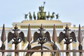 picture of winter palace  - Details of fence decoration with Russian Imperial Symbol of Double Headed Eagle at Palace Spuare behind blured view of gate to Palace Square St - JPG