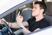 foto of middle finger  - Handsome Young Man Driving a Car and showing the middle finger - JPG