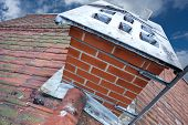 picture of red roof tile  - Close up of chimney on tiled roof with fungus on old worn roof tiles - JPG