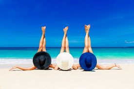 foto of slender  - Three young women in straw hats lying on a tropical beach stretching up slender legs - JPG