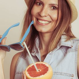 stock photo of flirty  - Happy glad woman tourist in straw hat holding sunglasses and grapefruit citrus fruit - JPG
