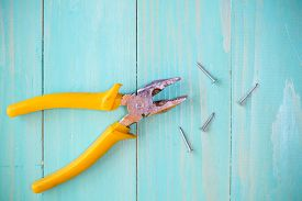 foto of nail-cutter  - Yellow pliers and few nails on wood background - JPG