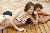 stock photo of young men  - A young couple on a sundeck on the beach relaxing - JPG