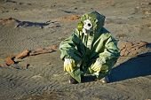picture of scoria  - Scientist in a green protective suit and gas mask sitting on the slag - JPG
