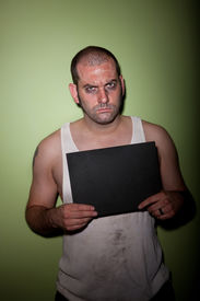 pic of wife-beater  - Man in wife beater takes mugshot with blank board - JPG