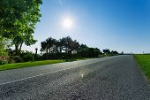 Empty Asphalt Country Road Passing Through Green Fields And Forests. Countryside Landscape On A Sunn poster