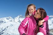Portrait of little girl embracing her mother on snowy mountain with copy space. Young smiling mother poster
