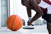 Determined basketball player tying shoelace poster