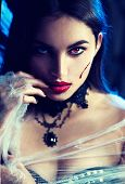 Beautiful Halloween Vampire Woman portrait. Beauty Angry Sexy Vampire Witch lady with blood on mouth poster