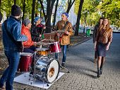 Festival music band. Friends playing on percussion instruments in autumn city park. Fountain and tre poster