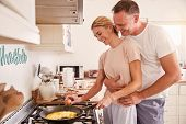 Affectionate Mature Couple Prepare Breakfast In Kitchen Together poster