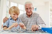 Senior man and grandson doing a jigsaw puzzle at home poster