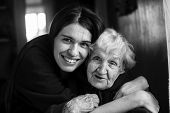 Elderly woman in an embrace with his adult daughter. Black and white portrait. poster