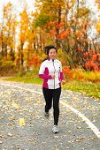 Middle aged mature Asian woman running healthy lifestyle Chinese lady run jogging in fall park in he poster