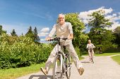 active old age, people and lifestyle concept - happy senior couple riding bicycles at summer park poster