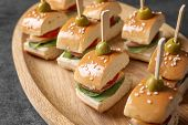 Mini burgers for baby shower party on wooden plate poster