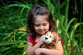 stock photo of stuffed animals  - Four year old girl cuddling with her stuffed animal tiger - JPG