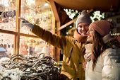 holidays, winter and people concept - happy couple at christmas market shop window in evening choosi poster