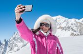 Young woman taking a selfie in winter holiday in mountain. Smiling snowboarder woman taking selfie w poster