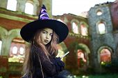 Sneaky little witch with magic wand looking at camera against shabby ruins poster