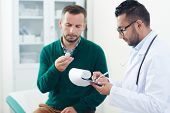 Profile view of confident young doctor in eyeglasses prescribing pills to middle-aged bearded patien poster