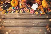 Sweets for Halloween and fresh pumpkin on wooden table with copy space. Trick or treat poster