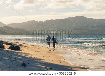poster of Couple Of Travelers Walking On Tropical Beach In Sunset. Vintage Photo Of Young Couple Traveler In V