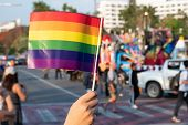 Lgbt Pride Month Background. A Spectator Waves A Gay Rainbow Flag At Lgbt Gay Pride Parade Festival  poster