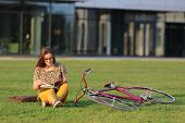 Young Female Student In Glasses With Backpack And Book Sitting On The Lawn. Young Female Have Lunch  poster