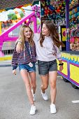 Candid photo of two cute and smiling teenage girls having fun at an outdoor carnival or theme park.  poster
