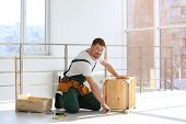 Handyman In Uniform Assembling Furniture Indoors. Professional Construction Tools poster