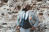 Handsome Bald Bearded Black Senior In An Elegant Costume In Front Of A Grungy Wall Outdoors; A Fashi poster