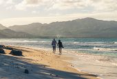 Couple Of Travelers Walking On Tropical Beach In Sunset. Vintage Photo Of Young Couple Traveler In V poster
