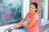 Young Colombian Woman Scrapes With Paint Scraper Over Window Frame poster