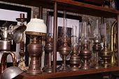 Many Kind Of Colorful Lamps On Wooden Shelf, The Paraffin Lamp Or Hand-held Lanterns Used In The Pas poster