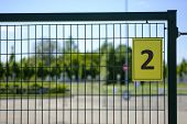Number Two (2). Yellow Plate With The Number 2 On A Metal Fence. House Number Two Sign poster