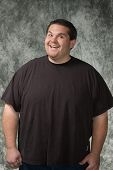 picture of obese man  - overweight young man posing in front of portrait backdrop - JPG