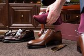 Trying new tight shoes. Man is putting on a new pair of luxury brown full grain leather shoes at foo poster