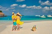 Family on beach, young couple in yellow with three year old boy. Summer vacation at Maldives. poster