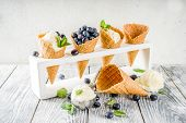 White Vanilla Ice Cream Balls With Ice Cream Cones, Spoon, Fresh Blueberry Berries And Mint Leaves,  poster