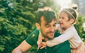 Outdoor Image Of Happy Cute Little Girl Smiling And Playing With Her Father. Handsome Dad And Pretty poster
