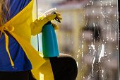Person Spraying Window Cleaning Detergent In Spray Bottle. House Clean Products, Household Care Equi poster