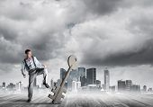 Determined Businessman Against Modern Cityscape Breaking With Leg Stone Key Figure poster