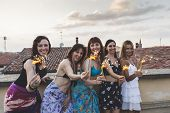 Group Of Happy Female Friends Holding Sparklers At Rooftop Party poster