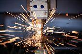 Laser cutting. Metal machining with sparks on CNC laser engraving maching poster