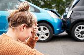 Female Motorist With Head In Hands Sitting Next To Vehicles Involved In Car Accident poster