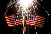 Lit sparkler over two American Flags for 4th of July celebration poster