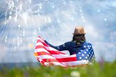 Young happy patriot girl holding the american flag under the 4th of July fireworks.  poster
