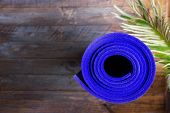 Blue Rolled Yoga Mat Lying On Wooden Background With Green Palm Leaf. Fitness Harmony Meditation Wor poster