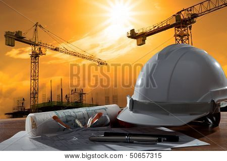 Safety Helmet And Architect Pland On Wood Table With Sunset Scene And Building Construction poster